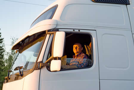 hand truck: The driver in a cabin of the truck in the evening Stock Photo