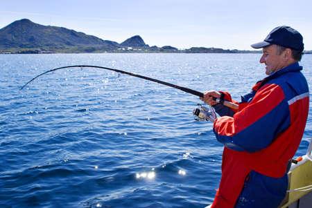 hombre pescando: Pescador con pescado en el barco cerca de la isla de las Islas Lofoten  Foto de archivo