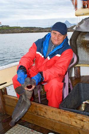 P�cheur avec poisson-chat sur le bateau pr�s de le �le Lofoten