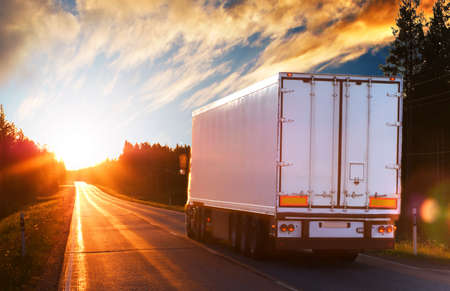 land transport: White truck on the asphalt road in the evening