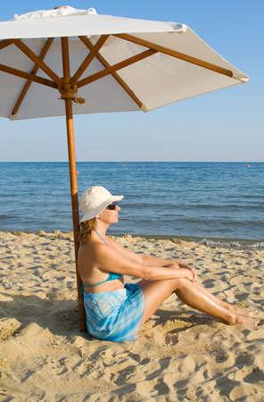 The woman under a solar umbrella on a beach photo