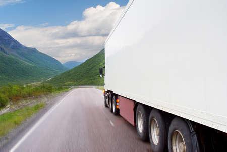 The white truck going on mountain road Stock Photo