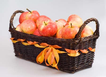 Le panier avec des pommes sur le fond blanc