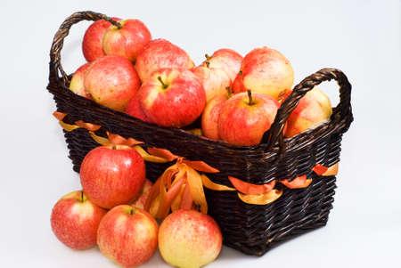 Panier avec des pommes rouges sur le fond blanc