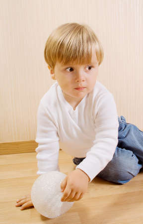 The child on the wood floor with white ball