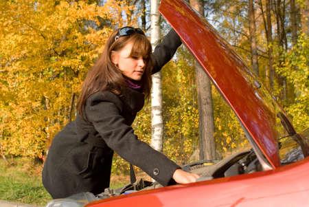 La jeune fille r�pare le moteur de la voiture