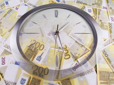 Une horloge et 200 euros billets sur un fond blanc