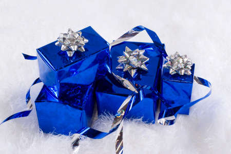 Blue shiny boxes for gifts with silver ribbons on the white skin photo
