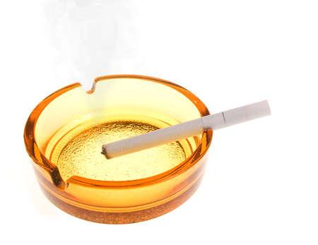 Smoking white cigarette in an ashtray on the white photo