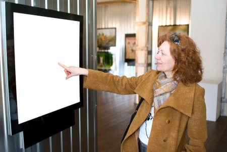 La femme redhead pointe vers une image