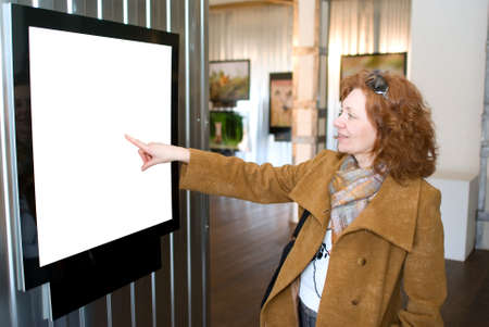 The redhead woman points to a picture photo