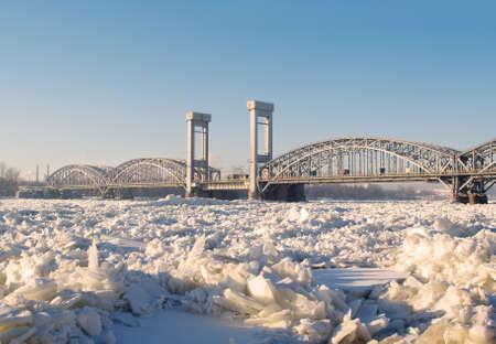 Railway bridge on the frozen river in sunny day Stock Photo