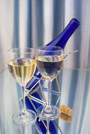 Deux verres de cristal de vin et une bouteille bleue