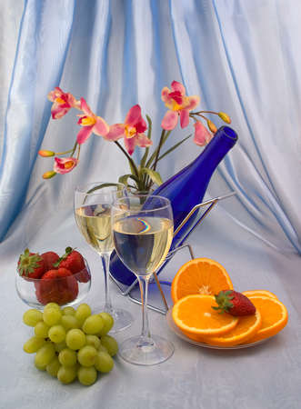 Two glasses of wine with fruits and orchid photo