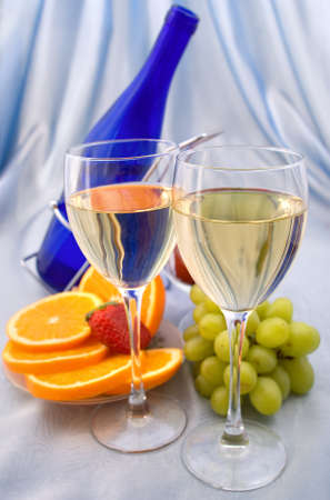 Two glasses of wine with oranges and grapes photo