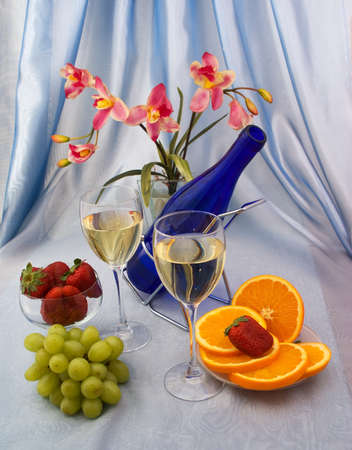 Glasses of wine with fruit and orchid photo