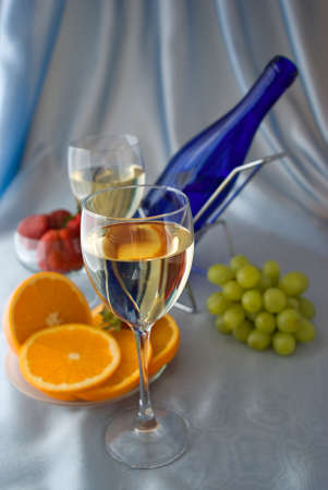 Glasses of wine with oranges and grapes photo