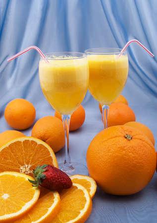 verre de jus d orange: Deux verres en cristal de jus d'orange frais avec des oranges et des fraises Banque d'images
