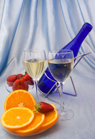 Two glasses of wine with oranges and strawberry photo