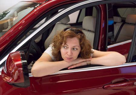 woman looks in a car mirror photo
