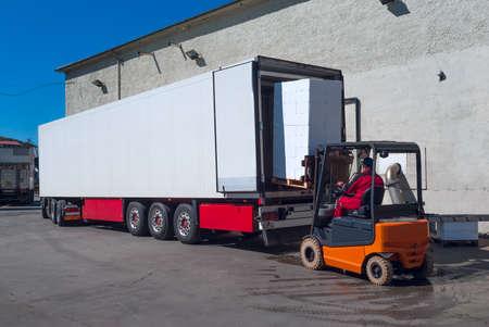 Worker on the loader unload white semi-trailer