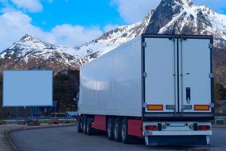 Bianco refrigerato camion su sfondo delle montagne e grande cartellone bianco