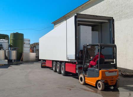 Worker on loader loads white semi-truck Stockfoto
