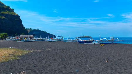 Boats on the beach of black sand on the island of Bali in Indonesia. Summer sunny day. Stock Photo