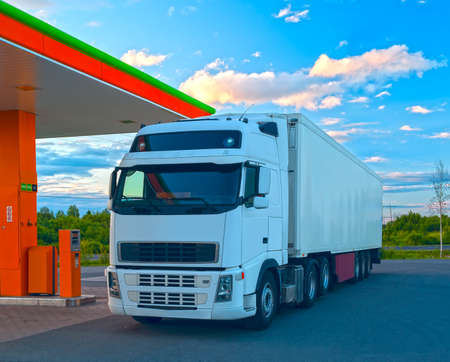 White truck is at the fuel station in sunny summer day