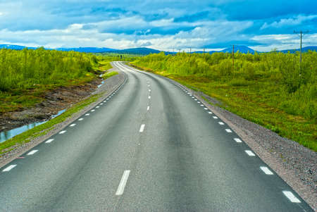 Grey sweden road to Norvegian mountains in sunny summer day Stock Photo