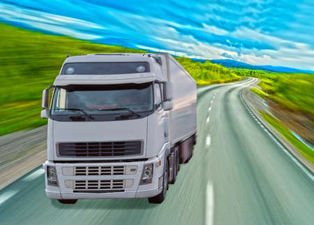 White truck moves along a road on a sunny day Stock Photo