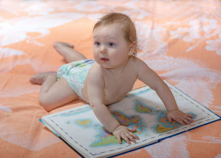 Small baby with big atlas maps of the world