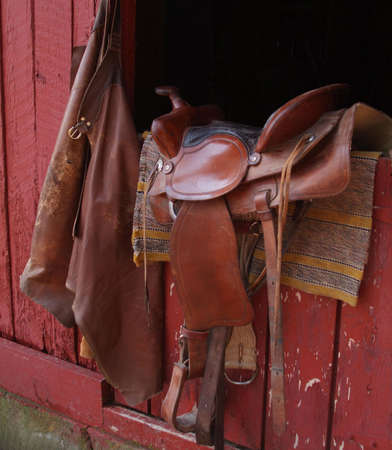 saddle and chaps on barn door with horse blanket