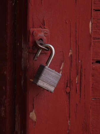 open pad lock hanging from old door