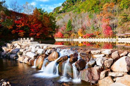 The waterfall in the autumn valley