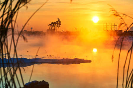 The oil sucking machines in the vapour lakeside under sunrise. Stock Photo