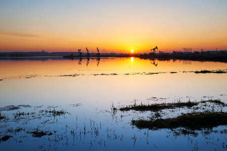 The oil fields by  lakeside with sunrise.