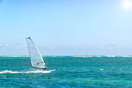 sailboard: Windsurfing. Windsurfer Surfing The Wind On Waves In Ocean, Sea. Extreme Sport Action. Recreational Sporting Activity. Healthy Active Lifestyle Stock Photo