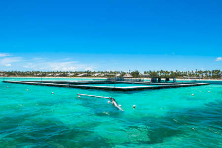 fish farm in the turquoise ocean with small waves, blue sky background Stock Photo