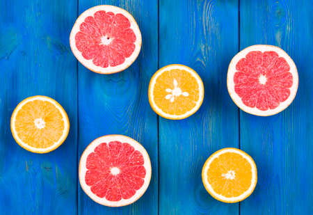 Fresh half cut grapefruit and orange on a blue wooden background, close up view Stock Photo