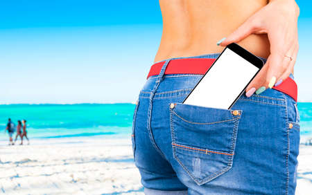 Smartphone with isolated white screen with empty space for text in a jeans pocket of a young beautiful girl, ocean background
