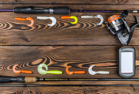 intend: Fishing tackle - fishing spinning, fishing line, hooks, navigator and reel on wooden background