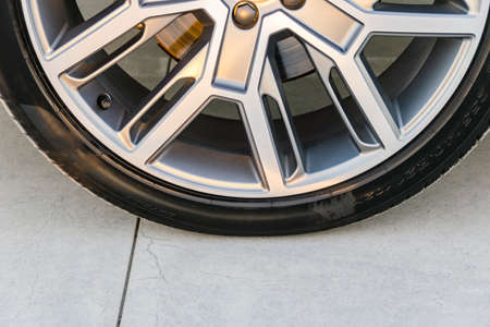 Tire and alloy wheel of a modern car on the ground, car exterior details