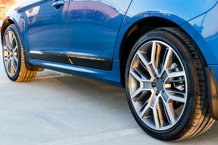 Tire and alloy wheel of a modern blue car on the ground, car exterior details