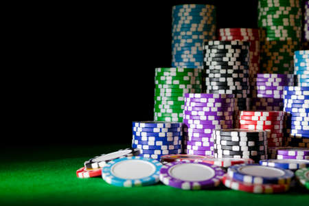 Stack of Poker chips on a green gaming poker table at the casino. Poker game concept. Playing a game with dice. Casino Concept for business risk, chance, good luck or gambling. chips for poker game