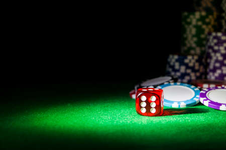 Stack of Poker chips on a green gaming poker table with poker dice at the casino . Playing a game with dice. Casino dice Concept for business risk, chance, good luck or gambling. chips and dice for poker