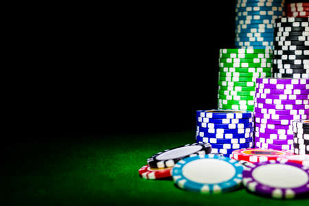 Stapel Pokerchips auf einem grünen Spielpokertisch am Kasino. Pokerspiel-Konzept. Ein Spiel mit Würfeln spielen. Casino-Konzept für Geschäftsrisiko, Chance, Glück oder Glücksspiel. Chips für Pokerspiel