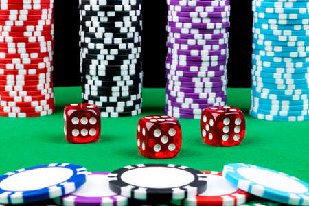 Stack of Poker chips on a green gaming poker table with poker dice at the casino. Playing a game with dice. Casino dice Concept for business risk, chance good luck or gambling. chips and dice for poker