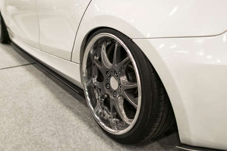 Tire and alloy wheel of a modern white car on the ground. car exterior details Stock Photo