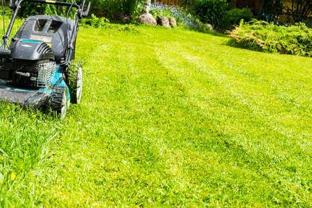 Het maaien van gazons, grasmaaier op groen gras, maaier gras apparatuur, maaien tuinman zorg werktool, close-up weergave, zonnige dag Stockfoto